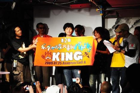 第2回「ギャグ漫画家大喜利バトル」キングの座に輝いたとり・みき。寺田克也より贈呈された勝者の証を掲げる姿は、王者の風格を漂わせている。