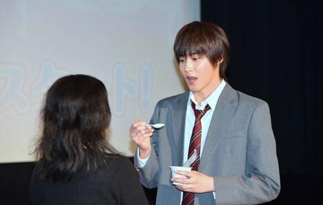 抽選で選ばれた来場者の口に、「あーん」と牛乳プリンを運ぶ白石隼也。