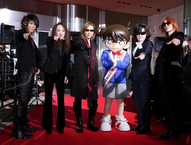 紅に染まったカーペットの上、「真実はいつも一つ」のポーズを決めるX JAPANと、Xポーズを披露する江戸川コナン。