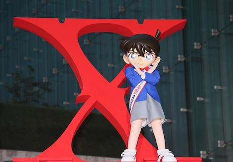 紅に染まった「Xロゴ」の前で、Xポーズを披露する江戸川コナン。