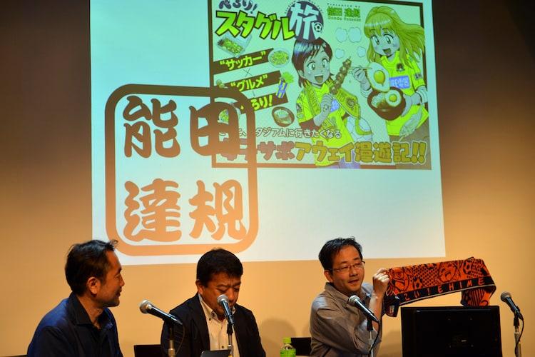 タオルマフラーを見せ愛媛FCサポーターであることをアピールする能田達規。