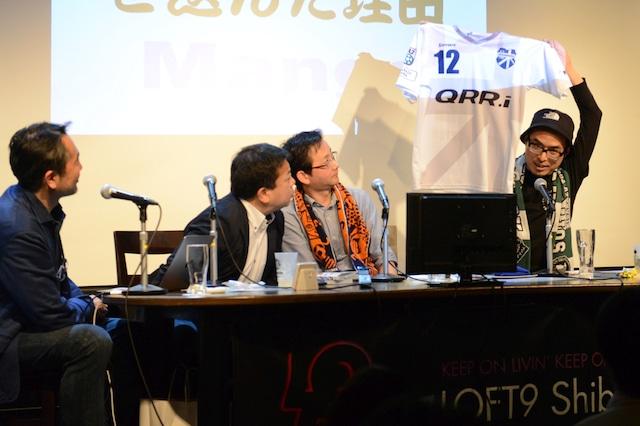 「サポルト!」のグッズのひとつ・ユニフォームを紹介する高田桂。