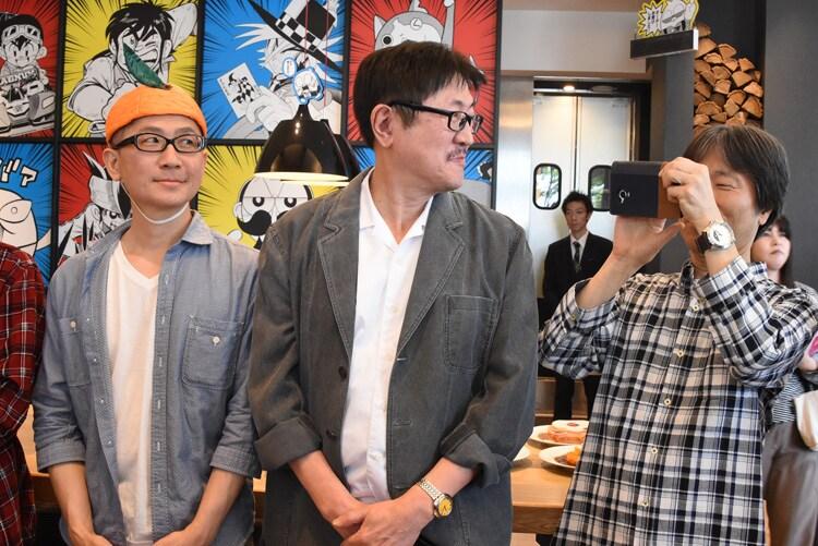 報道陣を撮影する沢田ユキオ(右)。