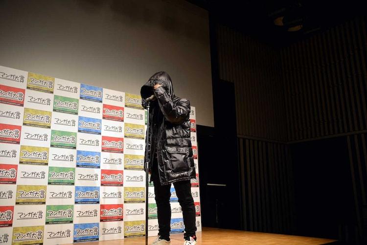 「響 ~小説家になる方法~」の主人公・鮎喰響のコスプレで顔を隠す柳本光晴。