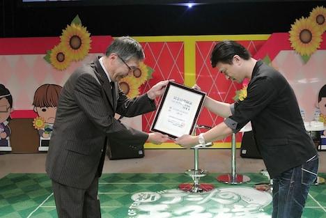 「ハッピーサマーバレンタインデー」の記念日登録証を受け取る許斐剛(右)。