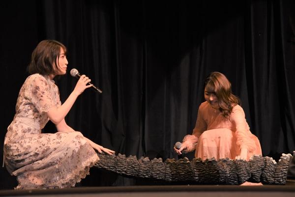 ゴジラのしっぽをなでる上田麗奈(左)、小澤亜李(右)。