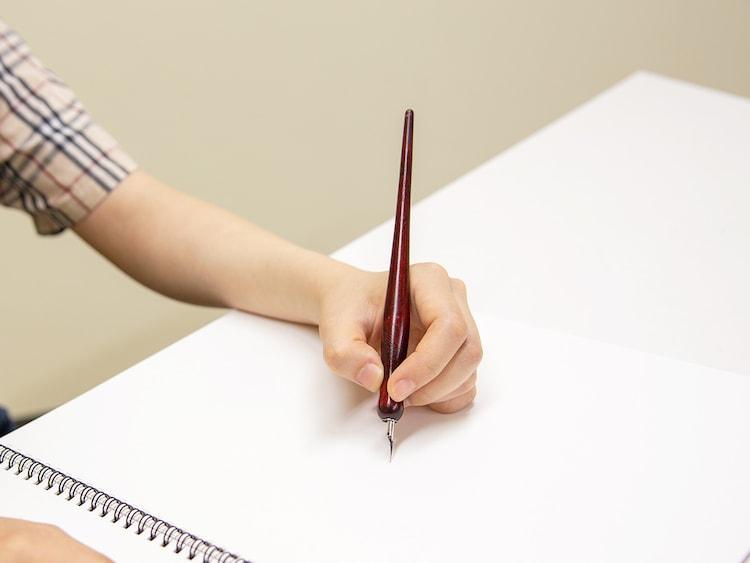 板垣巴留の手をかたどった石膏製モニュメントと、愛用ペン。