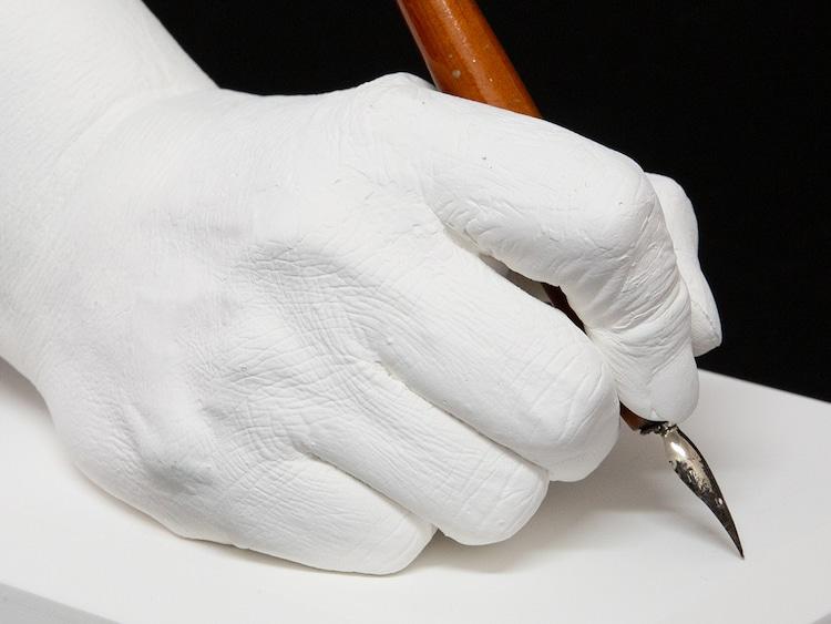 車田正美の手をかたどった石膏製モニュメントと、愛用ペン。