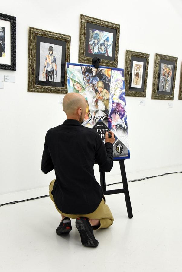 「画業30周年記念小畑健展 NEVER COMPLETE」のビジュアルにサインを入れる小畑健。