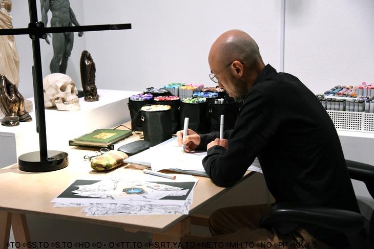会場で作画作業をする小畑健。