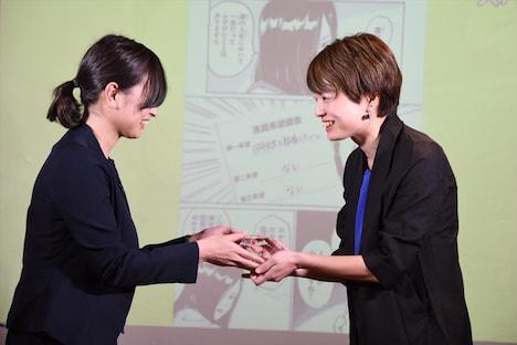 トロフィーを受け取る、「村井の恋」の担当編集者(右)。