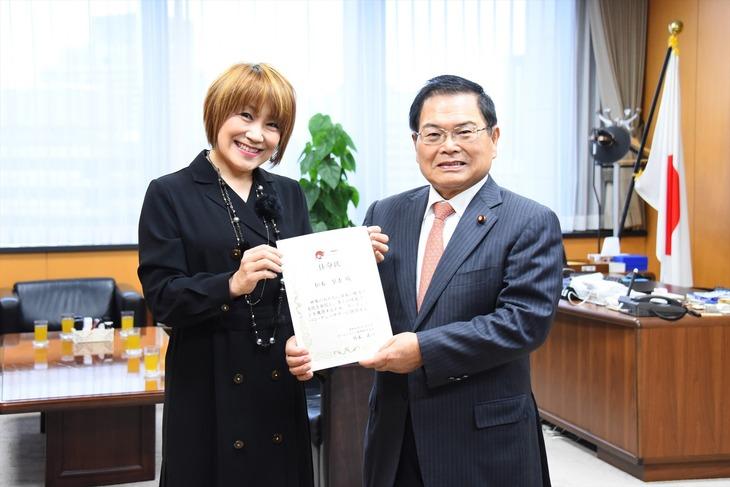 任命式の様子。左から松本梨香、竹本直一大臣。