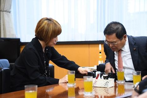 竹本大臣にライブ写真を見せる松本。