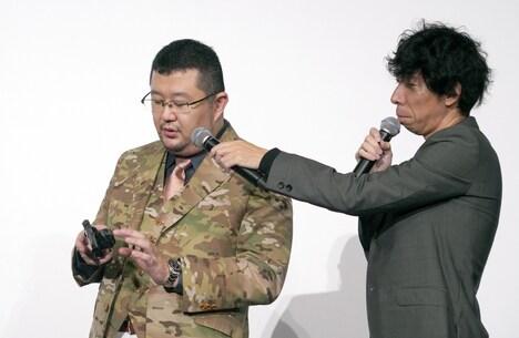 モデルガンを使ってリロードについて説明する金子賢一(左)。