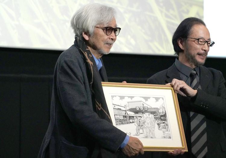 秋本治(右)からイラストを手渡される山田洋次監督(左)。