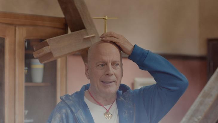 テレビCM「5Gって ドラえもん?『登場』篇」より、白戸家の屋根を突き破って登場したブルース・ウィリス扮するドラえもん。