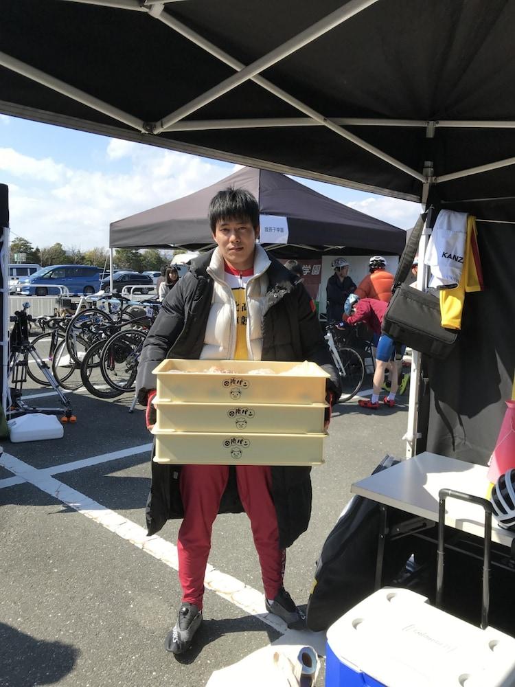 田所パンのパンを大量に持つ、田所迅役の菅原健。
