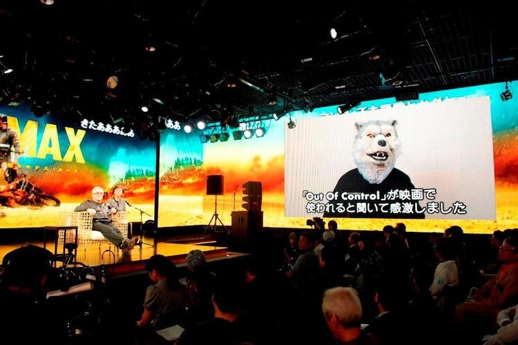 MAN WITH A MISSIONのJean-Ken Johnnyからのビデオメッセージを観るジョージ・ミラー。 (c)2015 VILLAGE ROADSHOW FILMS (BVI) LIMITED