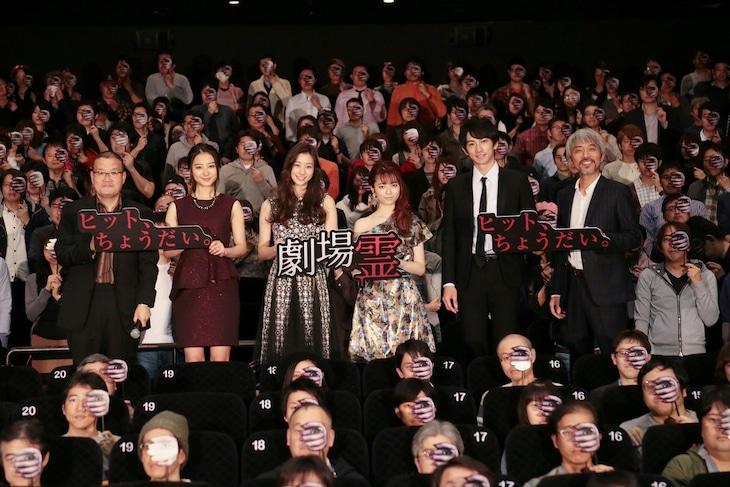 「劇場霊」舞台挨拶にて、ポスタービジュアルふうにデザインされた仮面を手にした観客と一緒に記念撮影するキャストと監督。