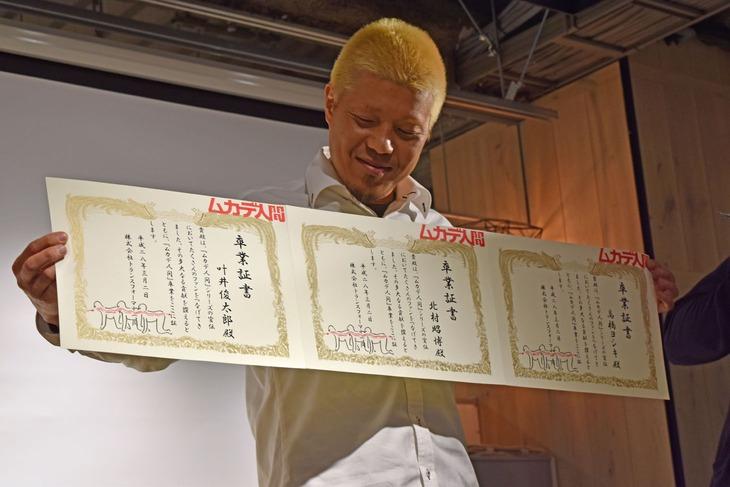 """""""ムカデ人間卒業証書""""を受け取った北村昭博。"""