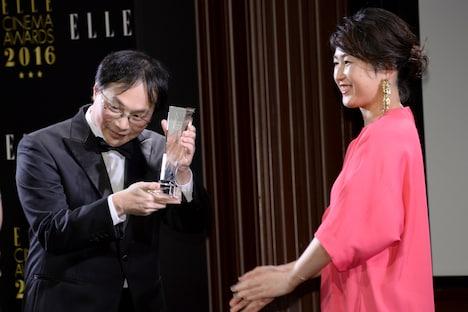 トロフィーを受け取る深田晃司(左)。