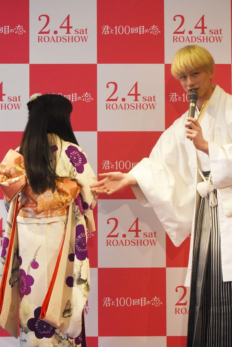 miwaを後ろ向きにさせ着物を紹介する坂口健太郎。
