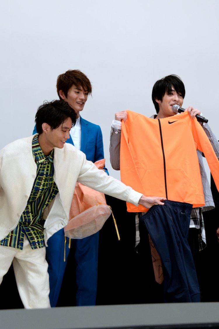 トレーニングウェアを体に当てる西銘駿(右)と、手伝う磯村勇斗(左)。