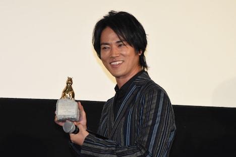 第67回ベルリン国際映画祭で贈られたトロフィーを手にする桐谷健太。