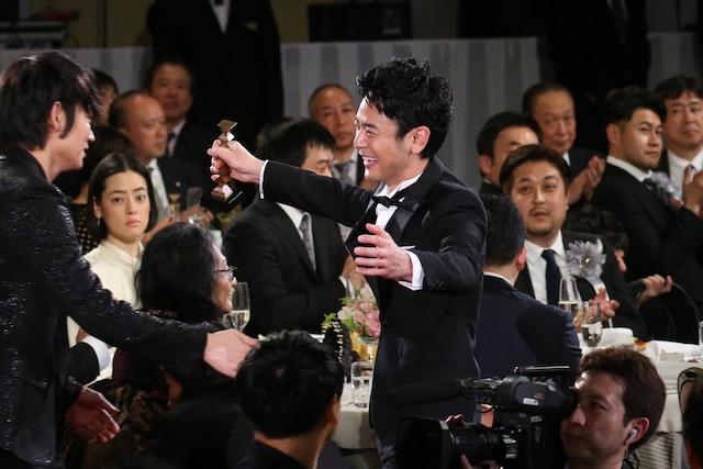 綾野剛と抱擁しようとする妻夫木聡(中央)。