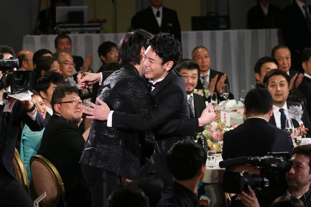 綾野剛と抱擁する妻夫木聡(中央右)。