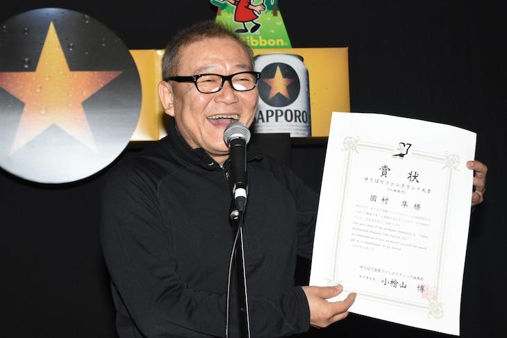 人物賞を受賞し、うれしそうに表彰状を見せる國村隼。