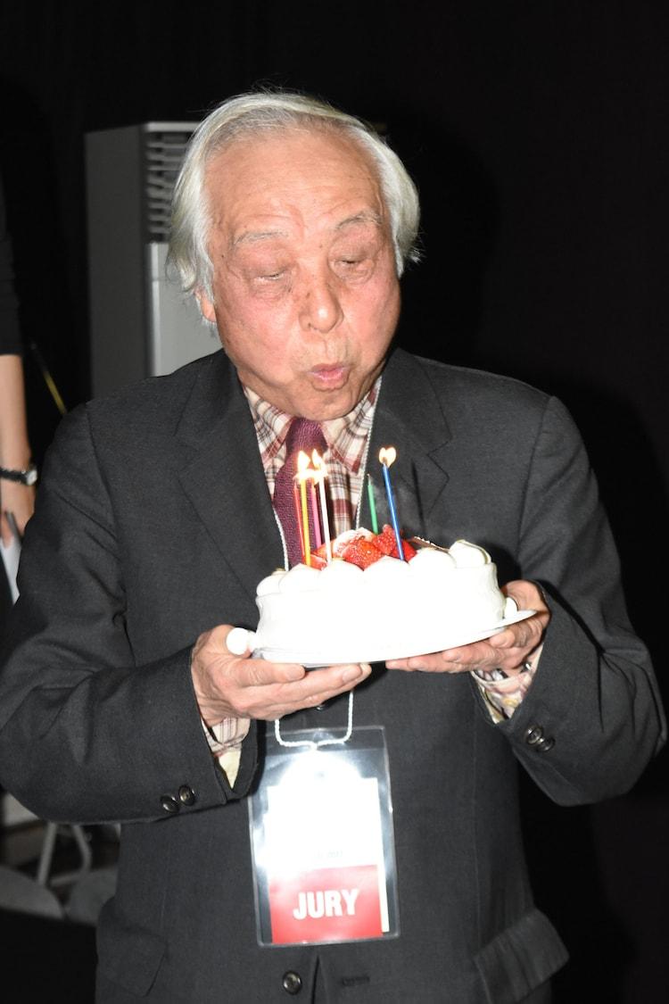 ケーキのろうそくを吹き消す内藤誠。