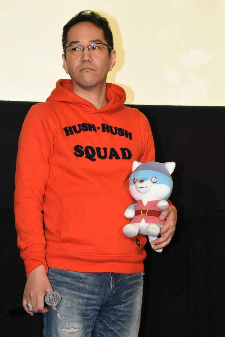 劇中キャラクター、ジョイのぬいぐるみを抱える神山健治。