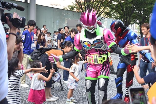 ハイタッチパレードに参加する仮面ライダーエグゼイド(手前)と仮面ライダービルド(奥)。