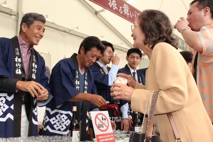 来場者に酒を振る舞う舘ひろし(左)、神田正輝(右)。
