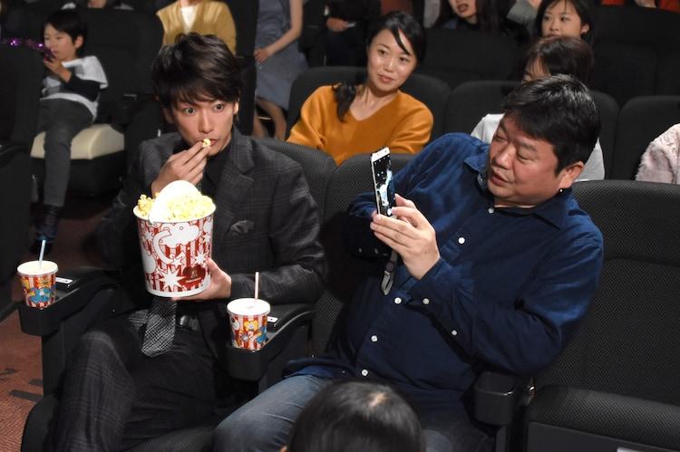 ポップコーンを食べる佐藤健(左)と、佐藤を撮影しようとする本広克行(右)。