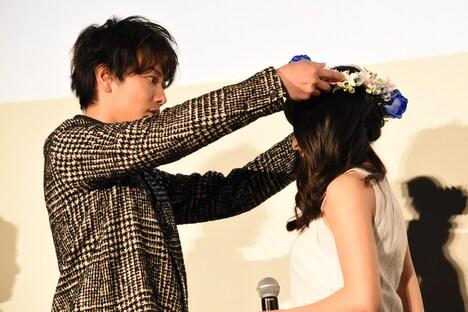 青いバラとダイヤモンドリリーで作られた花冠を土屋太鳳(右)に優しく被せる佐藤健(左)。