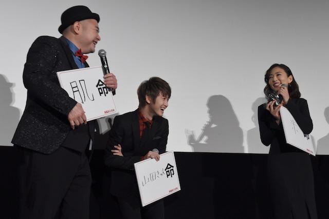 内山信二(左)からおにぎりを受け取った松雪泰子(右)。