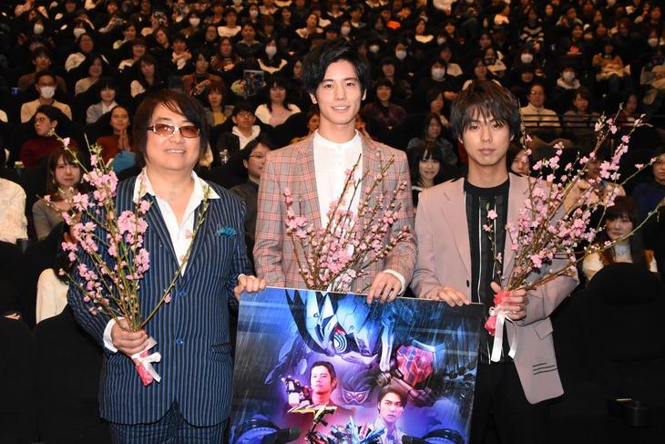 桃の花を持って写真撮影に応じる登壇者たち。左から鈴村展弘、岩永徹也、小野塚勇人。