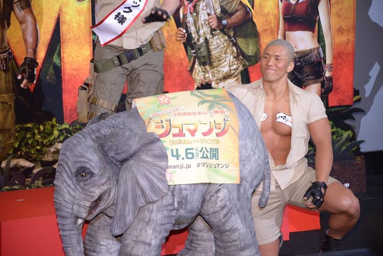 """左からミニサイズのゾウ、""""象使い""""の男性。"""