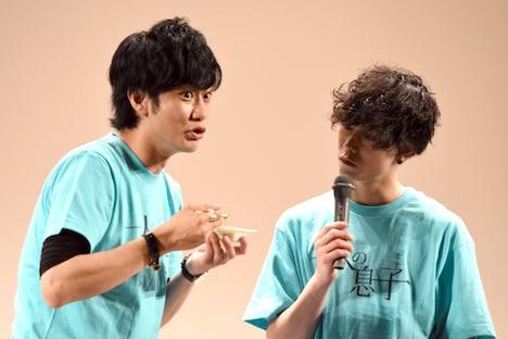 自分が提案した青汁メニューを食べる馬場良馬(左)、それを見つめる玉城裕規(右)。
