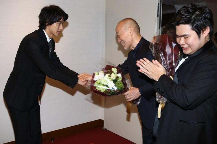 久石譲(中央)に花束を手渡す山崎賢人(左)。
