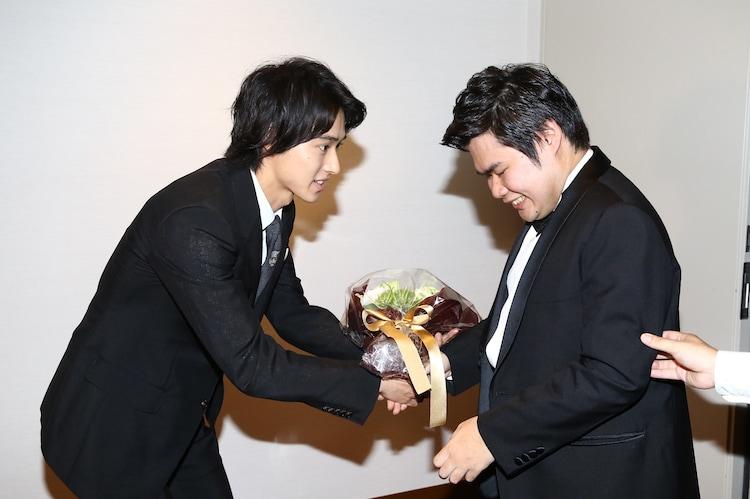 辻井伸行(右)に花束を手渡す山崎賢人(左)。