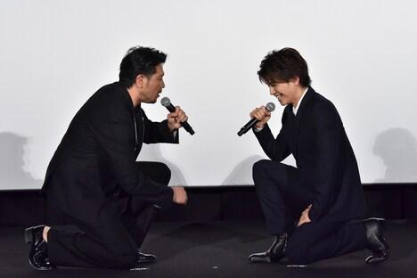 ひざまずいて向かい合う別所哲也(左)と岩田剛典(右)。