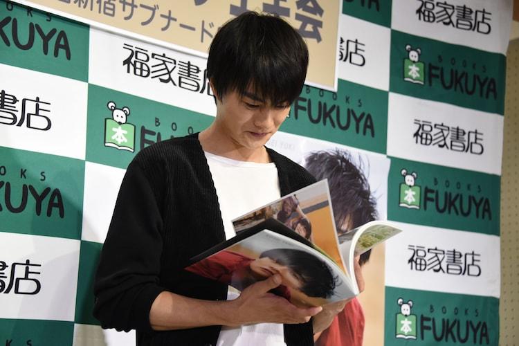 """""""沖縄×結木滉星""""というテーマに沿って、お気に入りのページを選ぶ結木滉星。"""