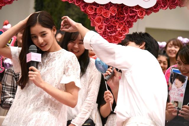 新木優子(左)の髪に付いた紙吹雪を取る吉沢亮(右)。