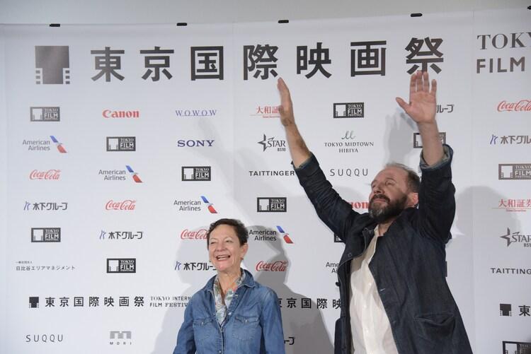 ムービーカメラへ大げさに手を振るレイフ・ファインズ(右)。