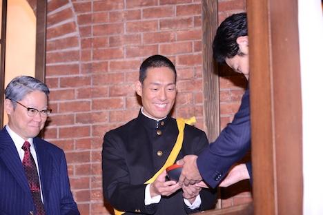 鈴木亮平(右)からさつま揚げを受け取る中村勘九郎(中央)。