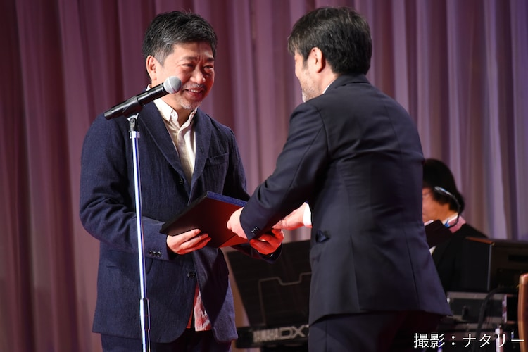 岸善幸(右)から表彰盾を受け取る是枝裕和(左)。