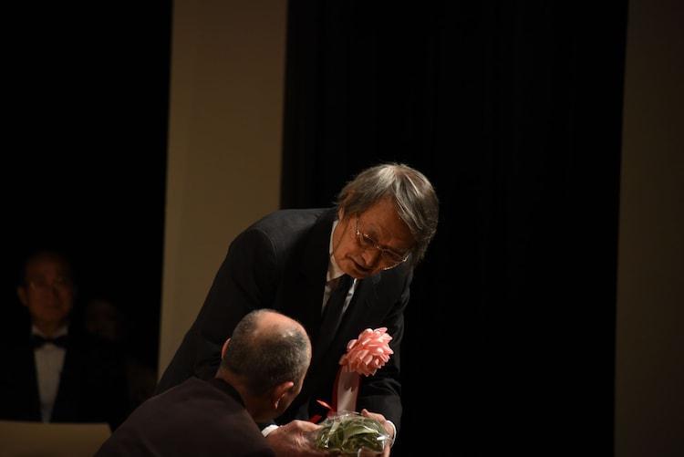 ファンから花束を受け取る山崎努。